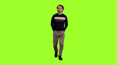 Elegant man walks with his hands in pockets on green screen background Footage
