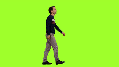 An elegant man in a striped sweater walks on green screen background Footage