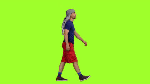 A male tourist in red shorts and arabic scarf walks on green screen background Footage
