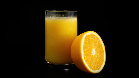 A glass of orange juice spins against a black background Footage