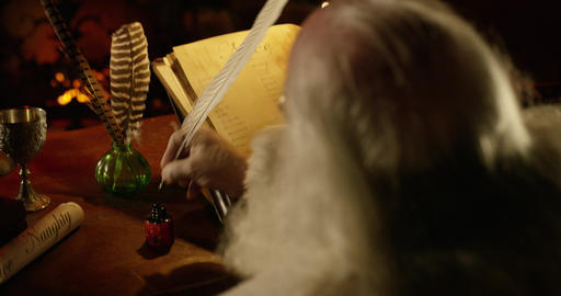 Santa Claus dips a quill pen in ink as he double checks his list. Over shoulder Footage