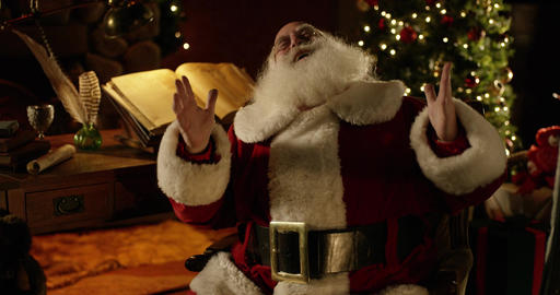 Santa Claus lets out a jolly laugh and throws his hands in the air Footage