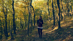 Static shot of young woman in black, sport outfit jogging in autumn colored Footage
