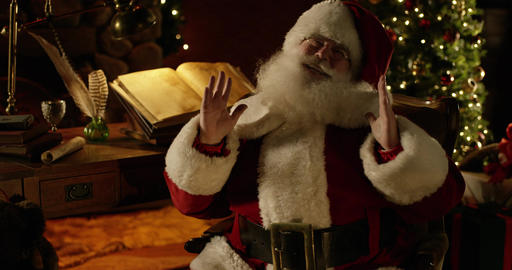 Santa Claus lets out a jolly laugh and gestures with both hands Footage