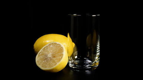 Fresh lemon juice poured into glass against black background Footage