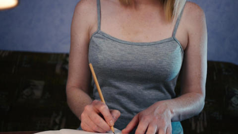 Young woman sitting at the table and thinks and writes Footage