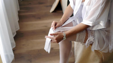 Bride pulling up stockings getting ready for her wedding in her bedroom - side ビデオ