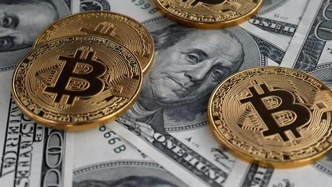 Gold Bitcoin BTC coins rotating on bills of 100 dollars Footage