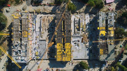 Aerial: above view of three cranes operating on the construction site. Camera Footage