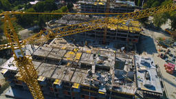 Aerial: camera tilting down over construction crane, and three buildings under Footage