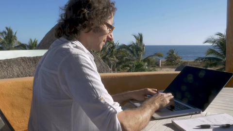 Digital nomad man working on laptop stops to answer smart phone with ocean view ビデオ