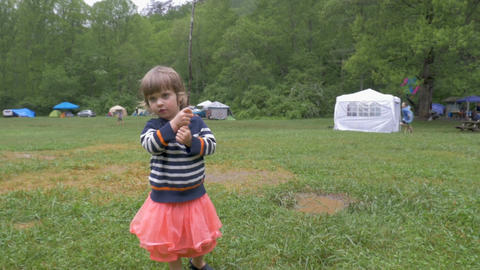 Adorable 2 year old girl in a pink skirt playing and pretending to fish with a Footage