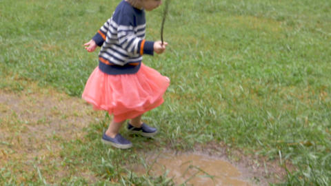 Cute little 2 year old girl in pink skirt running through puddle and looking at Footage