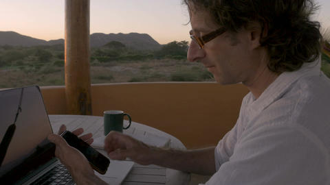 Handsome man working from remote office telecommuting along beach using laptop ビデオ