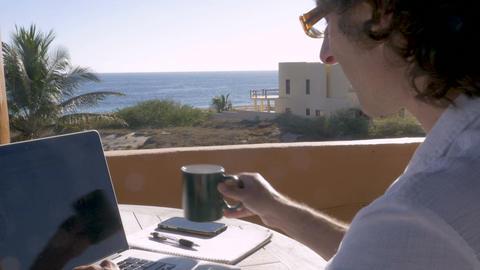 Entrepreneur man drinking coffee writing working and telecommuting on laptop ビデオ