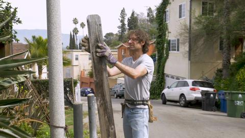 Man homeowner wearing work gloves repairing a fence outside a neighborhood in Footage