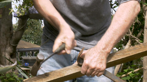 Active retired senior man reusing an old piece of wood removing rusty nails to Footage