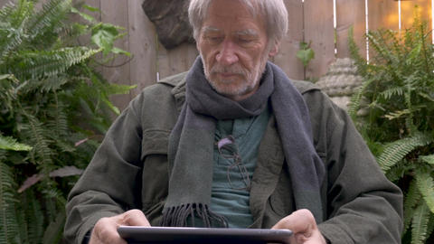 Vibrant healthy mature man in his 70s reading a digital tablet on his lap Footage