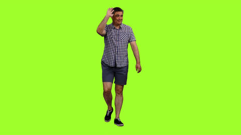 Male in shorts and plaid shirt walks and waving greetings on green background Footage