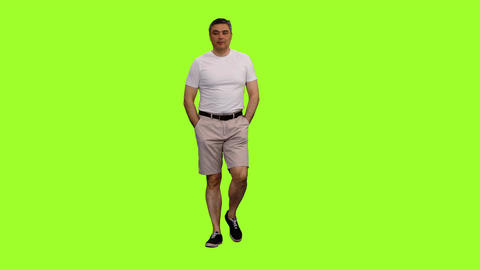A man in white t-shirt and shorts walks with hands in pockets on green Image