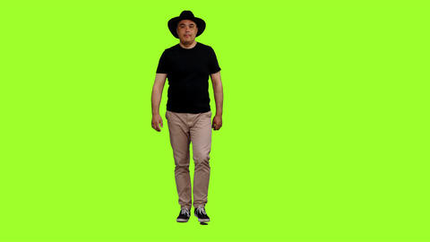 Adult man in black t-shirt and cowboy hat walks on green screen background Footage