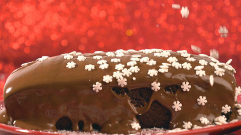 Candy snowflakes falling on chocolate cake on red background Archivo