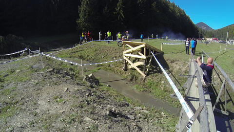 Motorcyclists jumping on a wooden trampoline during a motocross contest 02 Live Action
