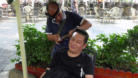 Man Practicing Traditional Ear Cleaning Earwax Removal In China Asia Filmmaterial
