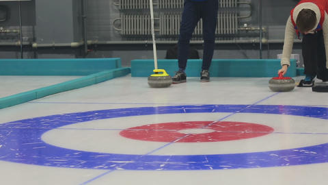 Girl curlers rolls a curling stone Live Action