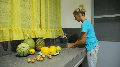 woman washing fruit at kitchen Footage