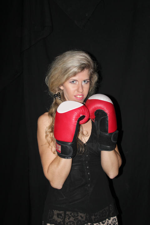blonde girl in black casual dress in boxing gloves フォト