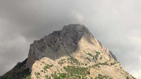 Time lapse clouds drift around and over mountain peak, Koba-Kaya Mountain Footage