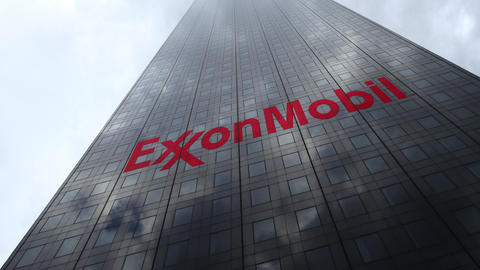 ExxonMobil logo on a skyscraper facade reflecting clouds, time lapse. Editorial Footage