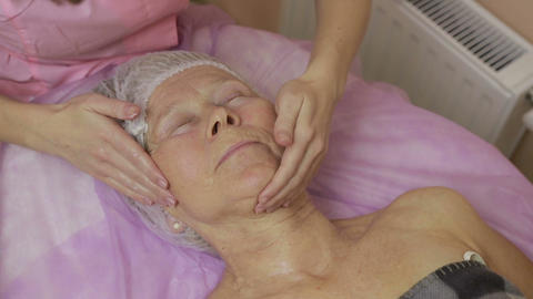 Relaxed elderly woman getting spa face treatment Footage