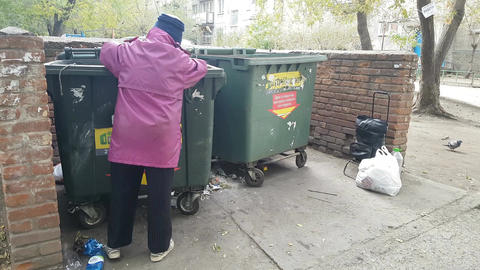 Old woman rummages in a garbage can Image