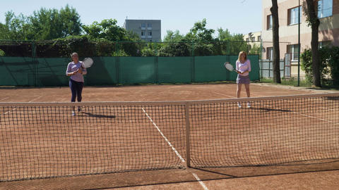Funny young women playing doubles at a tennis court Footage