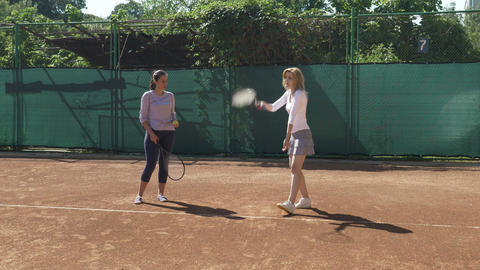 Young woman takes tennis classes and learns how to hold tennis racket and hit Footage