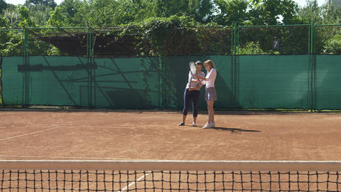Coach teaches tennis player to hold racket and serve Footage