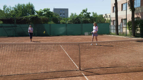 Two girl friends playing doubles tennis match winning and enjoying their triumph Footage