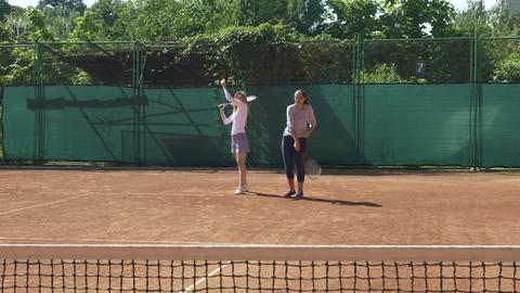 Player and her coach learning during a tennis class on the field Footage