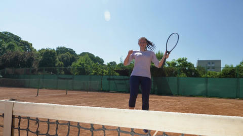 Winner of a tennis game comes to the fillet laughing happy holding her racket Footage