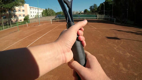 POV hands of tennis player holding racket and hitting ball in slow motion Footage