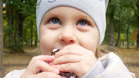 Beautiful Little Blonde Girl With Blond Hair And Blue Eyes Eats Chocolate Live Action