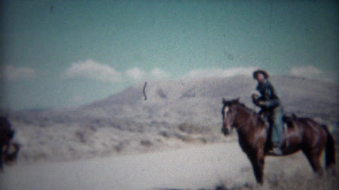 1956: Cowboy tips hat riding horse in western mountain range Footage