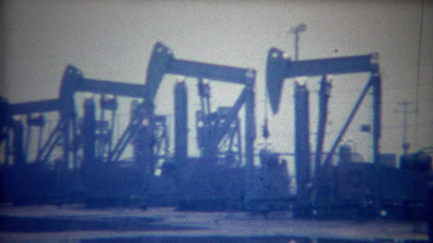 1956: Oil rig pump jacks sucking black gold crude underground Footage