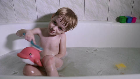 A little boy bathes and plays in the bathroom Live Action