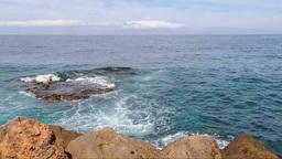 Serene Blue Sea, Waves Breaking Into Red Rocks Footage