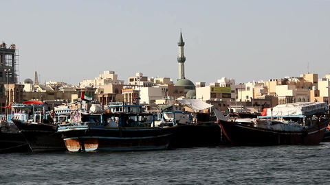 Dense urban old arab city houses, on shore, wood cargo dhow boats moored at bank Footage