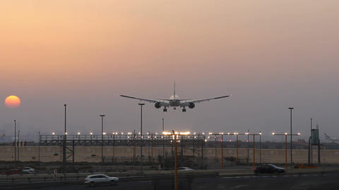 Airliner landing at airport, desert sunset view, straight runway perspective Footage