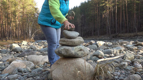 Woman putting pebble stack Footage